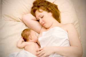Mum and baby on a bed breastfeeding