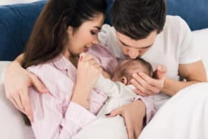 Couple on bed with breastfeeding baby