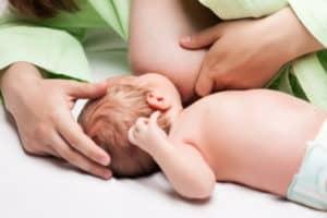 Baby breastfeeding - little newborn child sucking breast milk