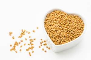 Fenugreek seeds in white bowl on white background