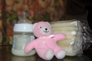 baby bottle with fresh expresed breast milk, frozen breastmilk in storage bags and soft toy pink teddy bear,