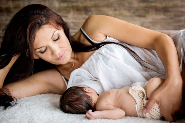 Mum lying down breastfeeding her baby